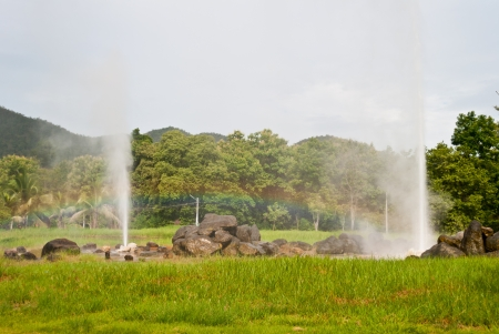 Geyser with rainbow and forest  photo