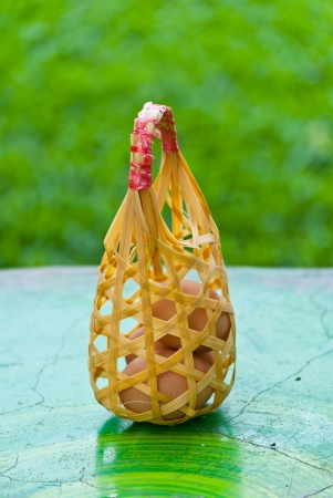 Eggs in basket on the table with green background  Stock Photo - 15515844