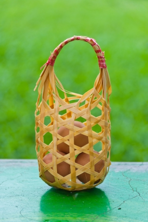 Eggs in basket on the table with green background Stock Photo - 15515846