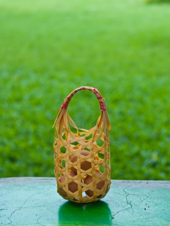 Eggs in basket on the table with green background Stock Photo - 15515729