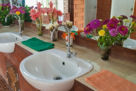 Closeup of  white sink and beautiful flower in modern bathroom