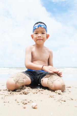playful boy on the beach with sea  on background