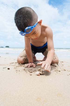playful boy and Hermit crab on the beach with sea  on background at Phuket island,Thailand Stock Photo