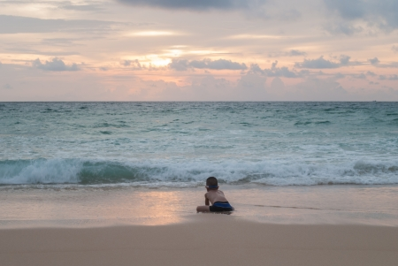 Lonely Asian boy on the beach with sea on background at Phuket island,Thailand