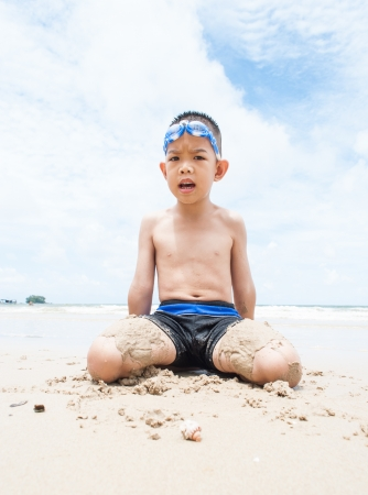 playful boy on the beach with sea  on background  photo