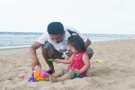 Baby asian girl with father playing with the sand on the beach.