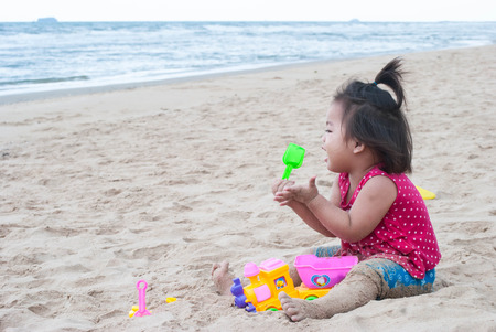 Baby asian girl playing with the sand on the beach.