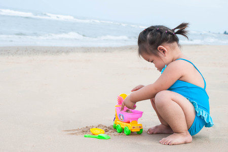 Asian baby girl playing with the sand on the beach. Stock Photo