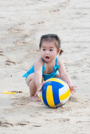 Asian baby girl playing football with the sand on the beach.
