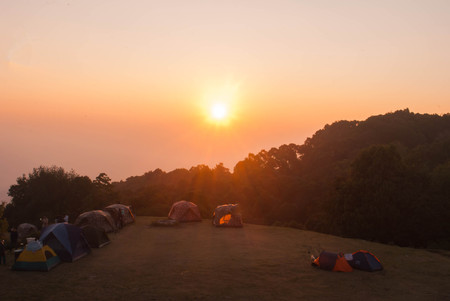 Tent camping in nature with sunrise over mountains at Huai Nam Dang National Park, Chiang Mai, Thailand. Stock Photo