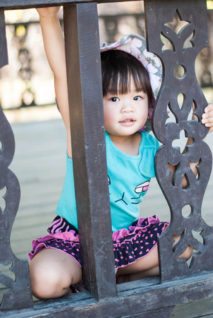 Shy Asian Little girl is looking out of the balcony. Stock Photo