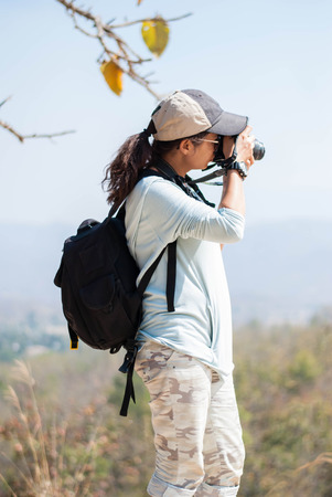 Outdoor summer smiling lifestyle portrait of pretty young woman having fun in mountain view in the north of Thailand  with camera travel photo of photographer Making pictures in hipster style. Stock Photo
