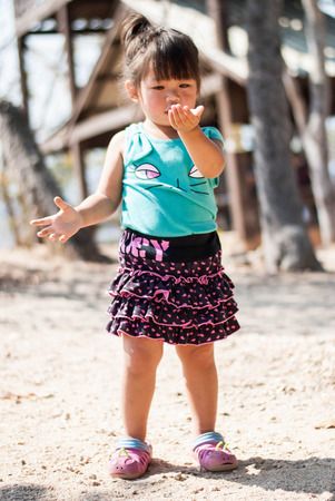 It is a sunny day outdoor. Beautiful little girl with pink skirt  is walking in the park.