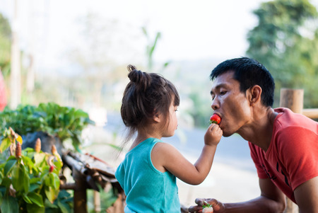 Little daughter giving fresh strawberry to her Father.