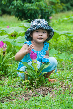 Cute asian girl with Siam tulips blooming in the forest at Chiang Mai province, Thailand