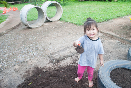 Little asia girl are Seeding or planting a plant on a natural, soil backgroud.