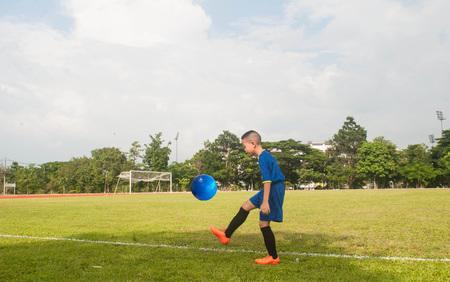 Asia boy playing Soccer football field stadium grass line ball background texture light shadow on the grass Stock Photo
