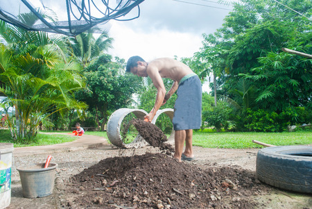 The man  working in the garden with the help of a shovel digging the ground in his house on a sunny day. Stock Photo