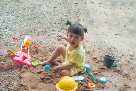 A little girl 4-5 years old is playing in the sand in the garden.