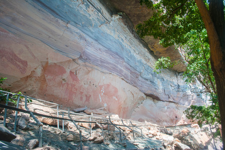 Ancient paintings on the old wall stone cave in ubon city of thailand. Stock Photo
