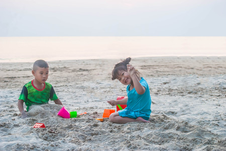 Asian little boy and girl are playing together on the sandy beach. Reklamní fotografie