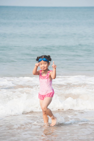Cute asia girl having fun on the sunny tropical beach with wonderful waves around her.