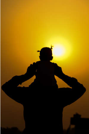 Silhouette of father carrying child