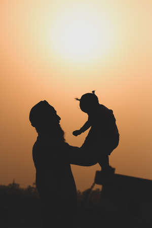 Father holding (carrying) the child playing by throwing up and catching. This is a silhouette of a father carrying a child showing a relation between them. Reklamní fotografie