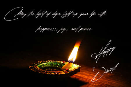 happy Diwali wishes with burning Diya on the black background
