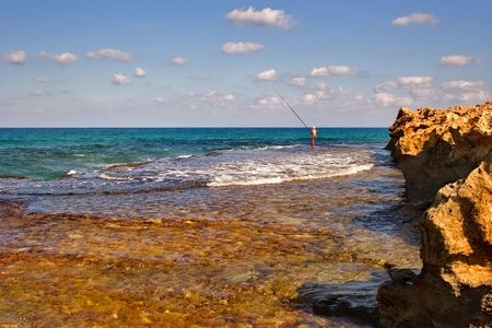 Lonely fisherman on a sunny sea shore Stock Photo - 555000