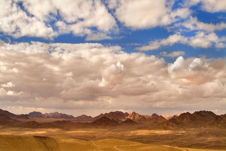 The sun and clouds above mountains of desert Sinai