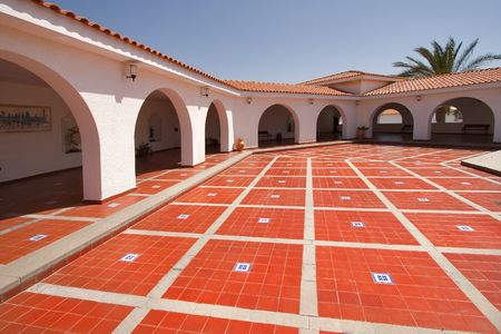 spanish style:  A red marble floor in a court yard in the Spanish style surrounded by gallery