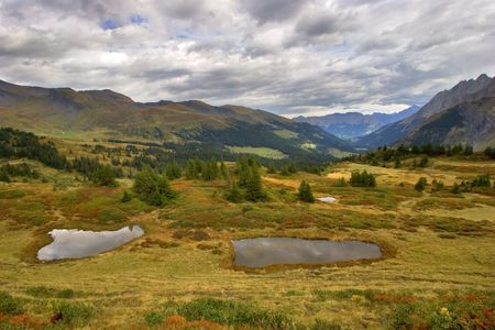 Small pools among the turned yellow grass in the Swiss Alpes photo
