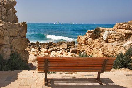 caesarea: A wooden bench on seacoast in ancient  port Caesarea in Israel