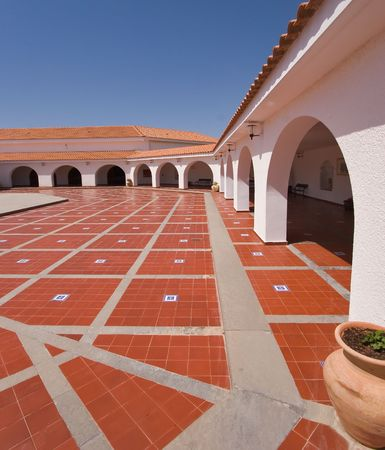 A red marble floor in a court yard in the Spanish style surrounded by gallery photo