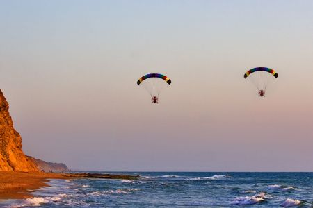Flight on an operated parachute along coast of Mediterranean sea Stock Photo - 1355391