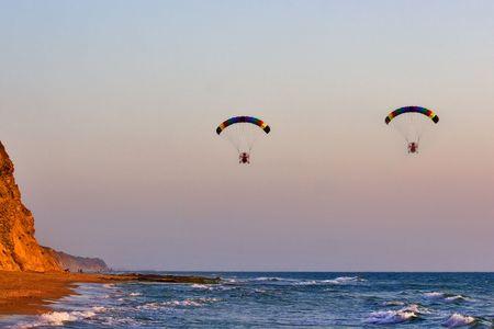 Flight on an operated parachute along coast of Mediterranean sea Stock Photo - 1355391