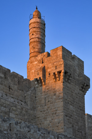 The ancient walls surrounding Old city in Jerusalem and the Tower of David, shined by the sun photo