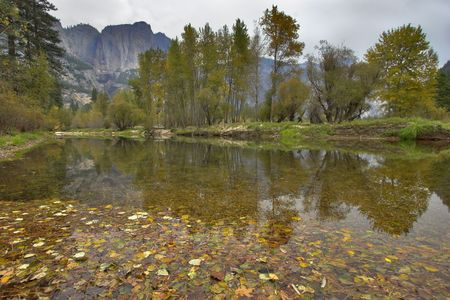 The mountain shallow lake which has been fallen asleep by yellow leaves