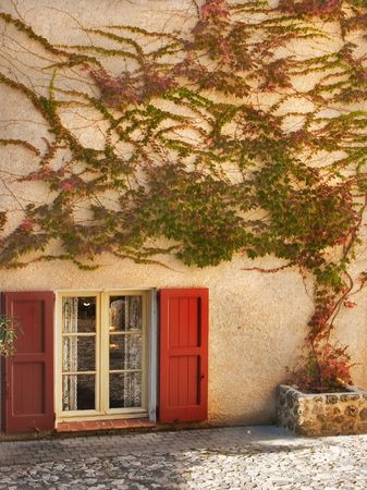 A window with red jalousie and branches of an ivy on a wall of the house in settlement Verdon photo