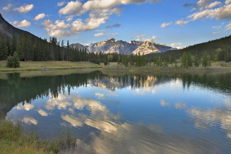 The sun shines tops of distant mountains and clouds above lake Stock Photo - 2374564