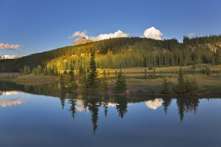 Charming lake in northern Canada, fur-trees and mountains photo