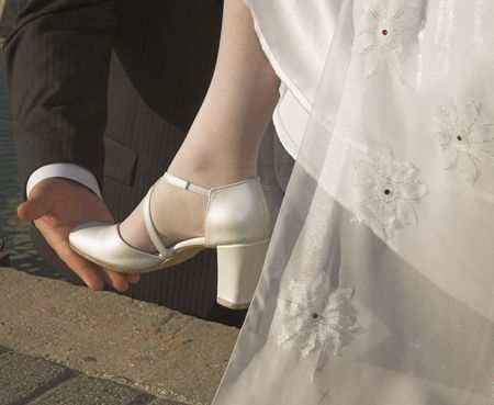 The graceful leg of the bride is supported with a hand of the groom photo