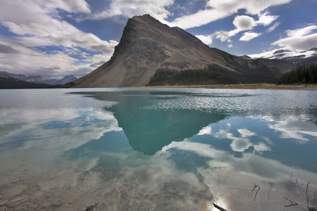 The huge rock of the triangular form is reflected in emerald waters of cold mountain lake Stock Photo - 2688254
