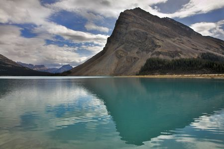 The huge rock of the triangular form is reflected in emerald waters of cold mountain lake Stock Photo - 2739310