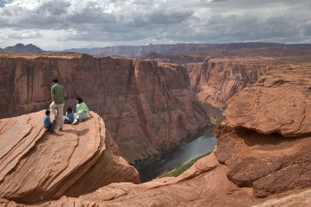 Group of tourists on edge of a deep canyon Horseshoe in state of Utah in the USA photo