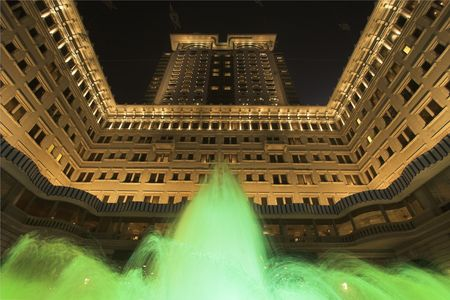 The jets of a fountain illuminated by green light before an enormous architectural complex in Hong Kong Stock Photo - 2847654