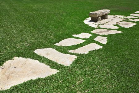 Path and stone bench in the middle of a grassy green lawn photo