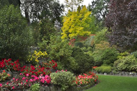 The green lawn surrounded by flower beds and blossoming trees Stock Photo