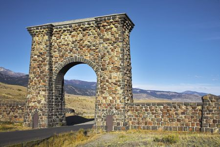 ascends: Huge stone gate on an input Yellowstone national park and when there ascends the sun